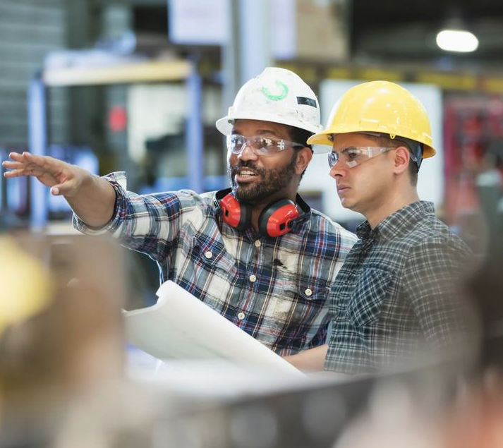 Photo of multi-ethnic workers talking in metal fabrication plant